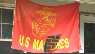 U.S. Marines flag still flying despite strong winds ripping roof off home