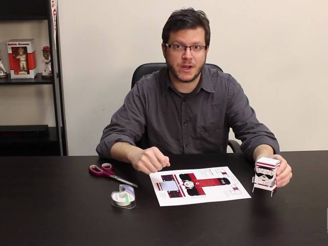 Kevin Necessary demonstrates how to put together Reds-themed pop-up toys…