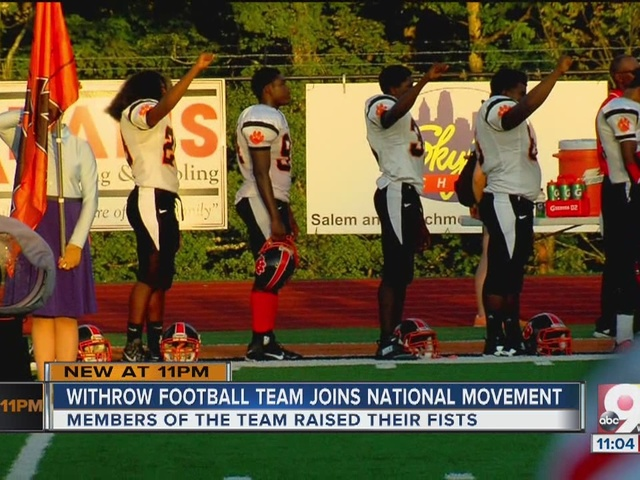 Withrow High School football players raise fists during national anthem
