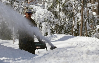 A man uses a snowblower to clear his driveway.